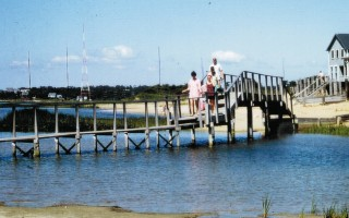 "A family crosses the footbridge to Cockle Cove and Ridgevale Beach in the late 1960s. Behind them are the transmitter towers from the old Marconi station. The photo is reprinted from the book, ""Images of Modern America: Chatham."" COURTESY M. MIKLUS  (photo: M. Miklus)"