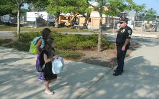 Sgt. William Massey greets Chatham Elementary School students on their first day of school. Massey is currently the police department's liaison officer with the schools, but also works a regular shift. Last week selectmen approved the addition of a full-time school resource officer to the department's roster, one of several steps Chief Mark Pawlina advocated for improving school security. FILE PHOTO  (photo: )