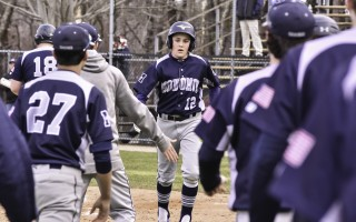 Brandon Willis (12) is congratulated by his Monomoy teammates after scoring a run for the Sharks against SJP2 on April 12.  (photo: )
