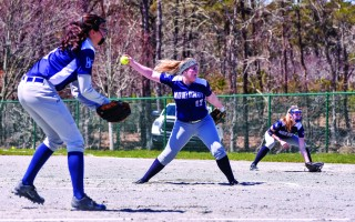 Monomoy pitcher Mollie Charest (17) takes aim as teammates Caroline DiGiovanni on third and Sam Barr on first keep an eye on the batter in the team's April 21 doubleheader against Bishop Fenwick. Kat Szmit Photo  (photo: )