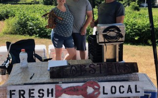 Shannon and Tyler Daley show off their lobster with mate John Booth at a recent farmer's market. 