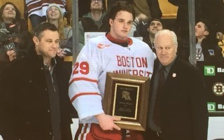 Dan Eberly (right) is joined by son Danny Eberly in presenting the 2017 Eberly Award to BU goalie Jake Oettinger following the Beanpot Tournament. CONTRIBUTED PHOTO  (photo: )