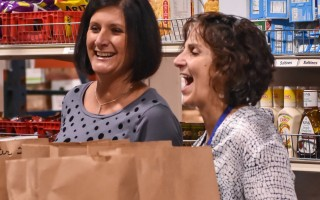 Family Pantry volunteers share a light moment while preparing bags of groceries for a client. FILE PHOTO  (photo: Kat Szmit)