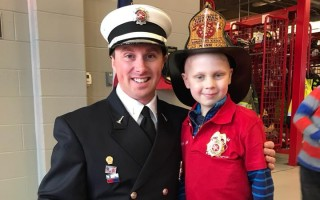 Jesse Nash with Firefighter Justin Tavano last December, when the 7-year-old was named the department's honorary chief. COURTESY PHOTO  (photo: )