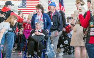 World War II Veterans Dorothy Raymond (in wheelchair) and Robert Raymond (behind her, in blue cap) receive a warm welcome at the Baltimore airport. COURTESY PHOTO  (photo: Joe Kelley, Honor Flight New England)