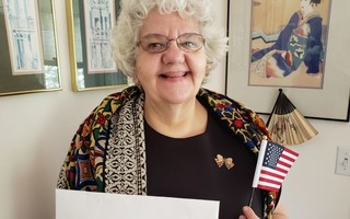 Carolyn Wass of Chatham celebrates her official citizenship with a wave of an American flag as she shows off her official documents. Wass is most looking forward to voting in the November election, believing this to be the year of change. PHOTO COURTESY OF CAROLYN WASS  (photo: )