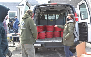 Division of Marine Fisheries protected species specialist Erin Burke, right, points out rolls of red weak rope given to fishermen Friday in Chatham. BRAD JOYAL PHOTO 