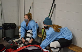 Nauset freshmen Sienna Reeves, left, and Bella Roberts tie their skates before a Cape Cod Furies hockey practice in February at Charles Moore Arena in Orleans. Protective facemasks were required equipment for student-athletes this year. BRAD JOYAL PHOTO  (photo: )
