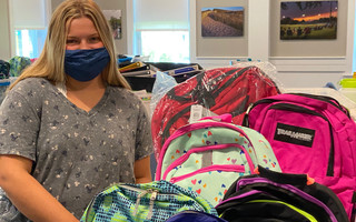 Volunteer Savannah with backpacks being stored at the Orleans Police Department, where they await distribution to students in the eight Lower Cape towns. COURTESY PHOTO 