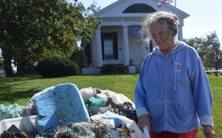 Rebecca Arnold surveys a skiff full of trash she collected from Chatham beaches. The skiff will be on the front lawn of the Chatham Unitarian Universalist Meetinghouse through the end of the month. TIM WOOD PHOTO  (photo: )