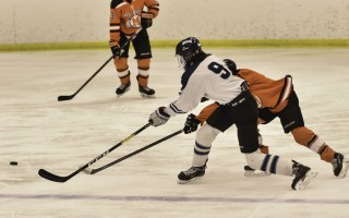 Monomoy's Cole Currie (9) knocks the puck away from a Middleboro/Hull opponent during game play Feb. 21 in Hyannis. Kat Szmit Photo  (photo: )
