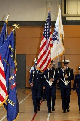 The U.S. Coast Guard's honor guard enters the assembly in the community center gymnasium Monday.
