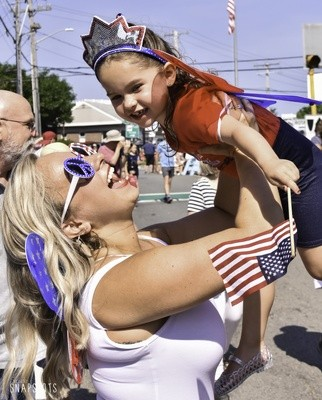 Ashley Armstrong shares a sweet moment with daughter Olivia as they await the start of the Chatham Fourth of July Parade.  KAT SZMIT PHOTO