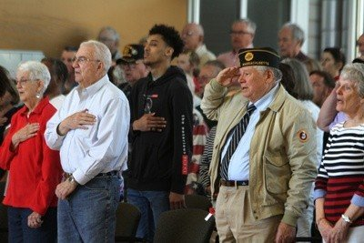 Veterans and other citizens salute the flag.